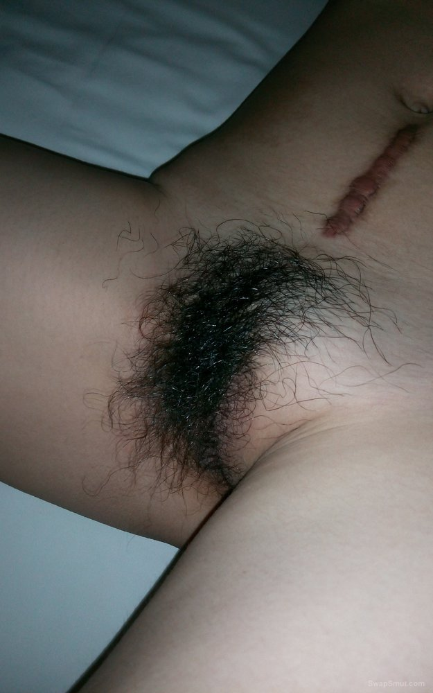 Hairy woman naked on the bed pussy hair glistening with creamy juices